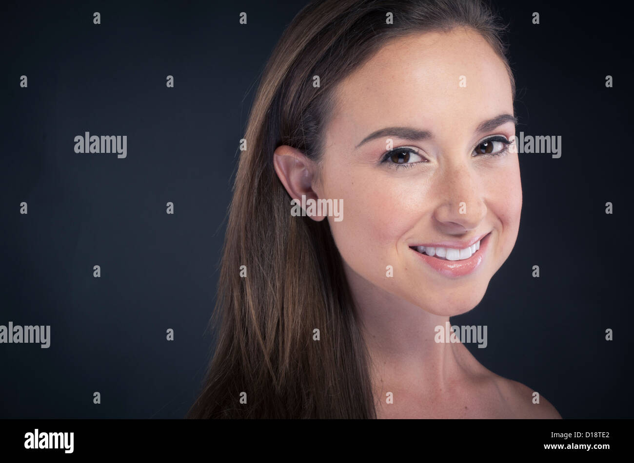 Young beautiful woman smiling on black background - Stock Image
