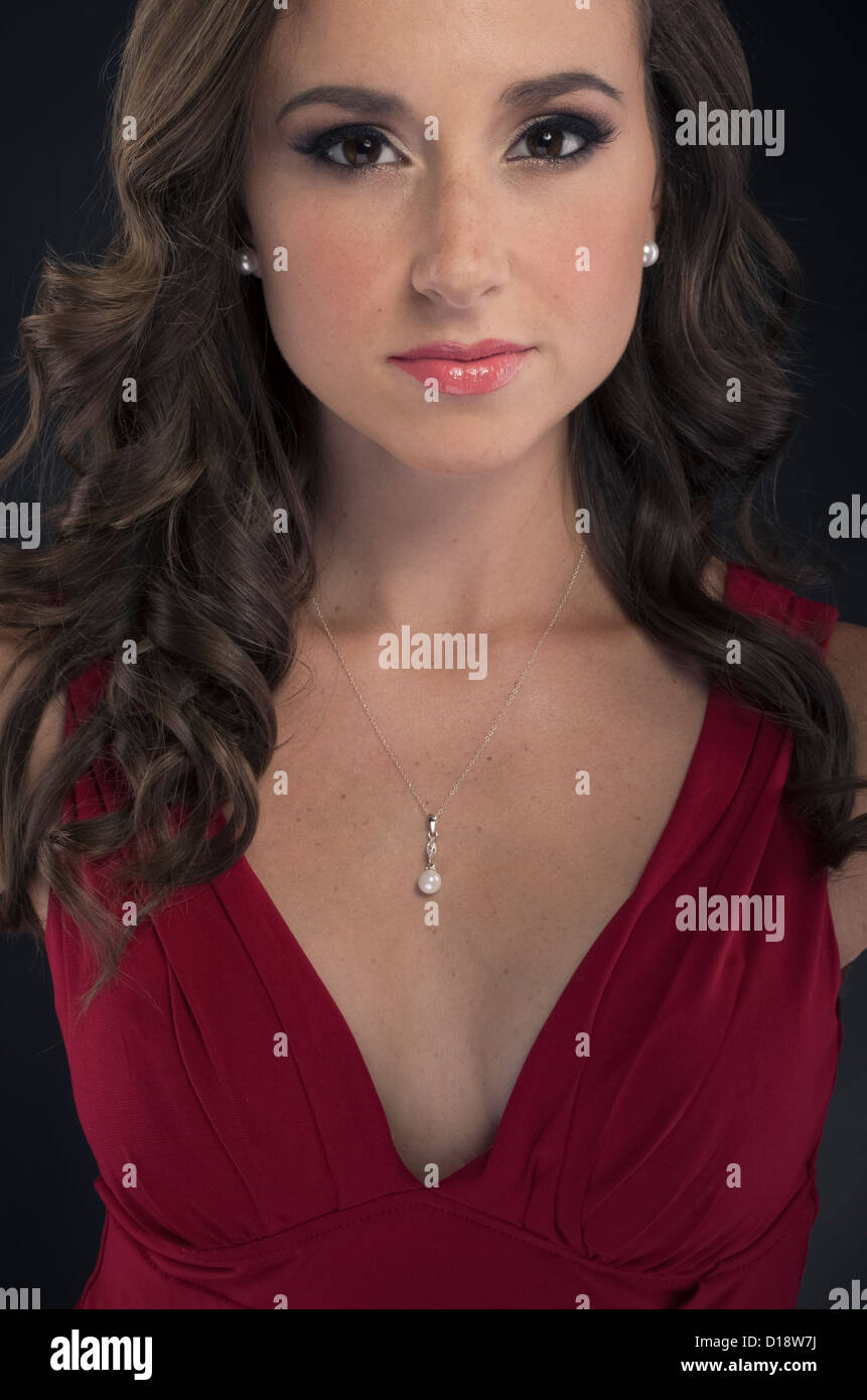 Woman with pearl earrings and simple necklace in red evening dress - Stock Image
