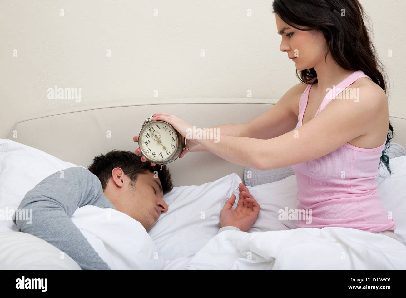 Couple in bed, woman holding alarm clock near mans head - Stock Image