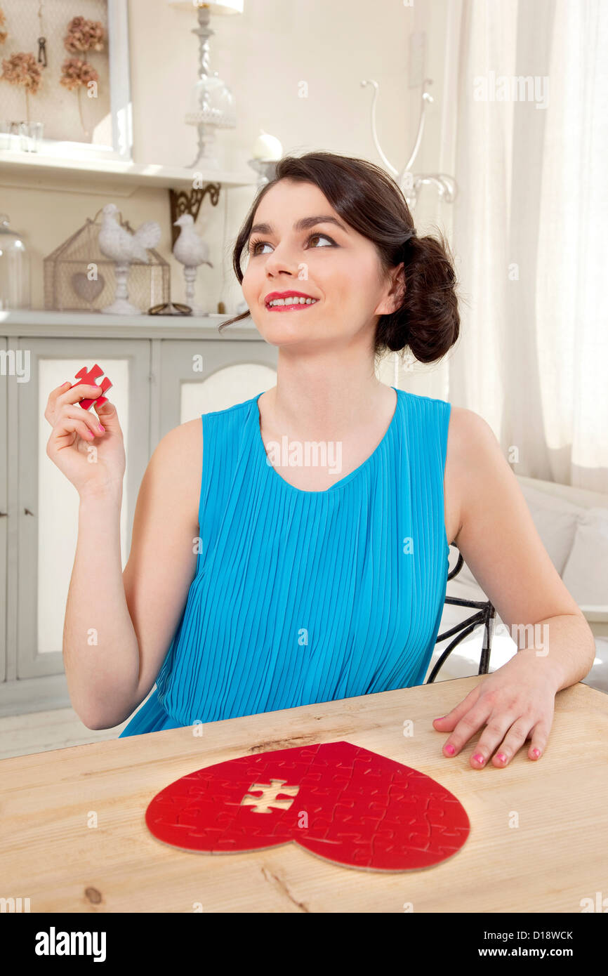 Woman doing heart shaped jigsaw puzzle holding piece Stock Photo