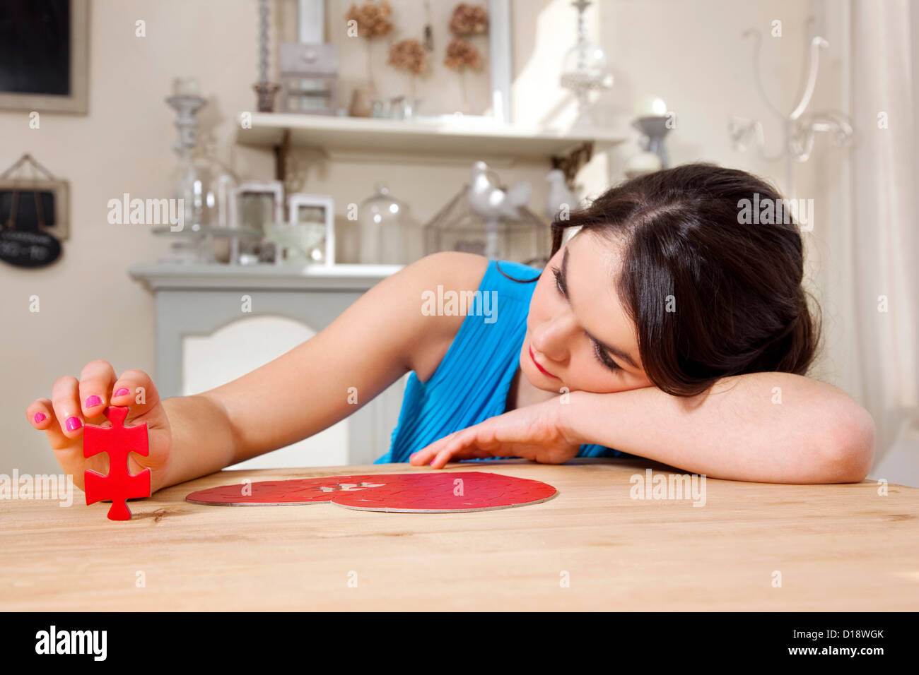 Woman doing heart shaped jigsaw puzzle Stock Photo