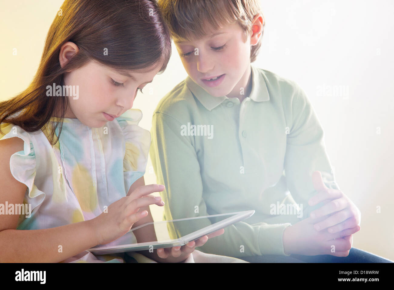 Girl and boy using digital tablet with bright light - Stock Image