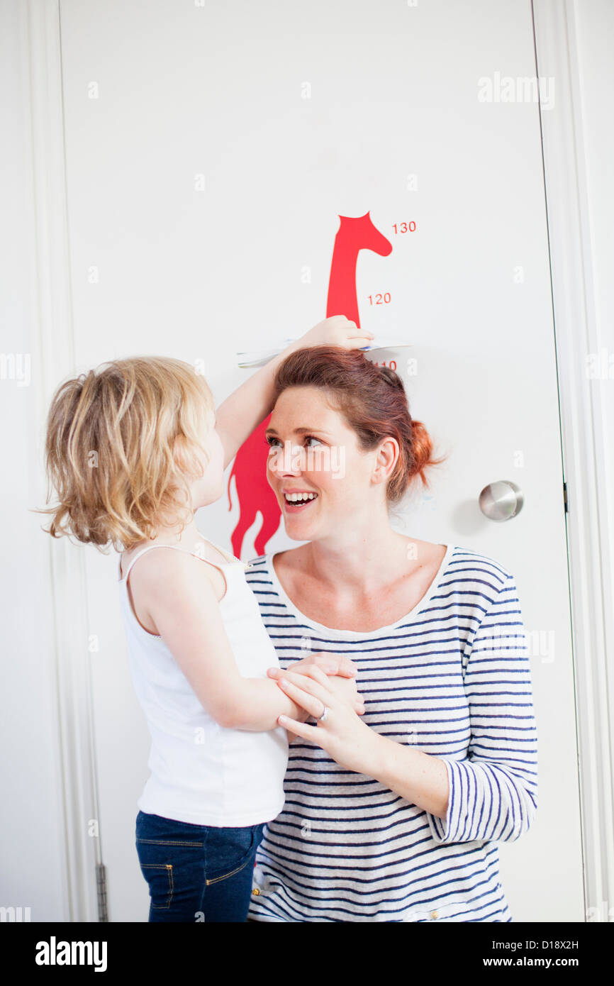 Daughter measuring mother on height chart - Stock Image