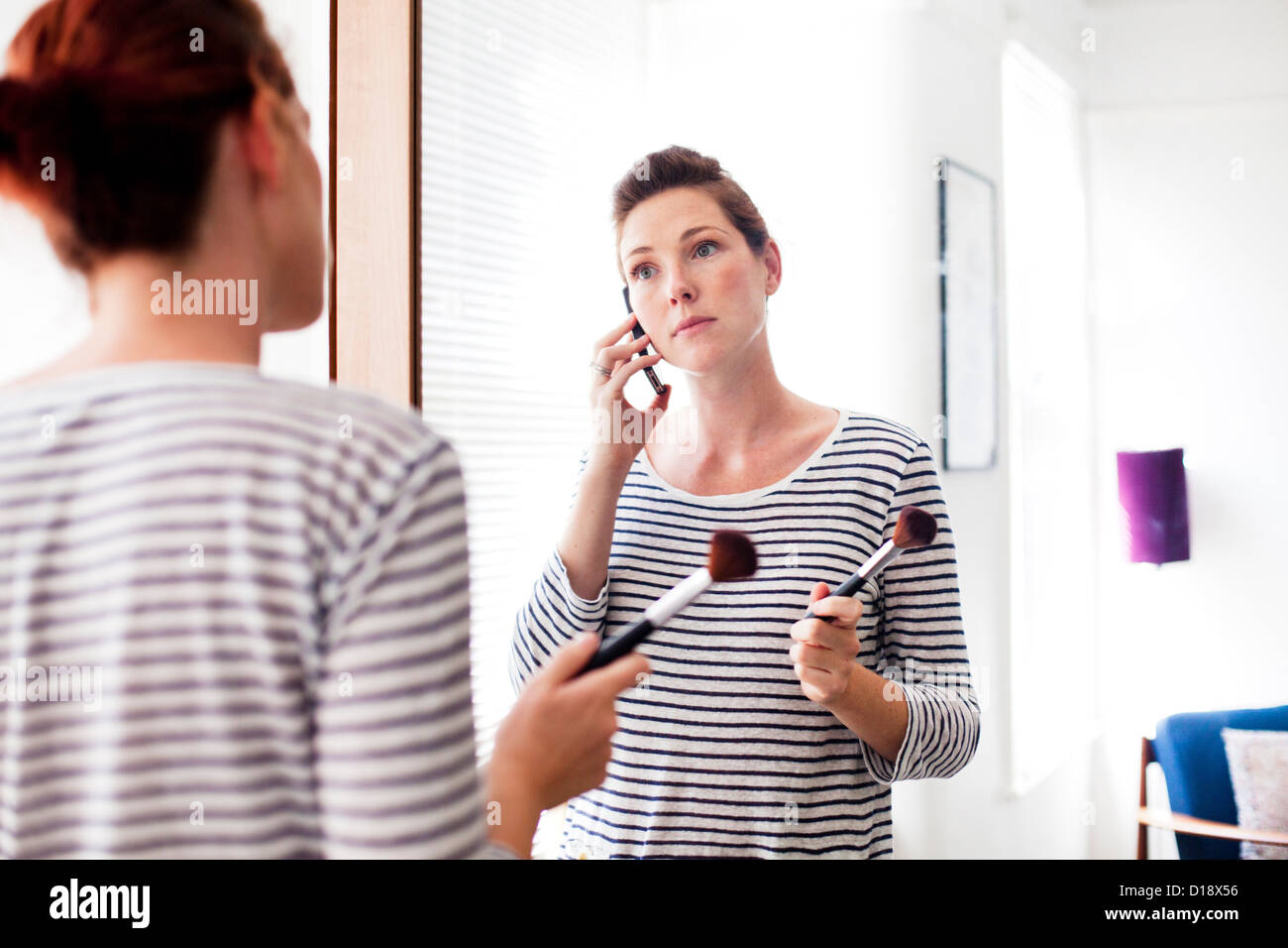 Woman on cell phone applying make up - Stock Image
