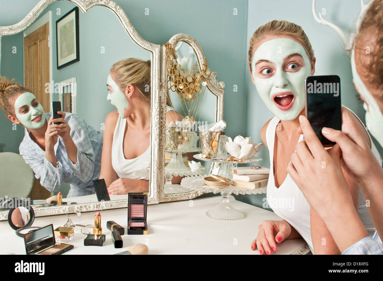 Woman wearing face mask being photographed by friend - Stock Image