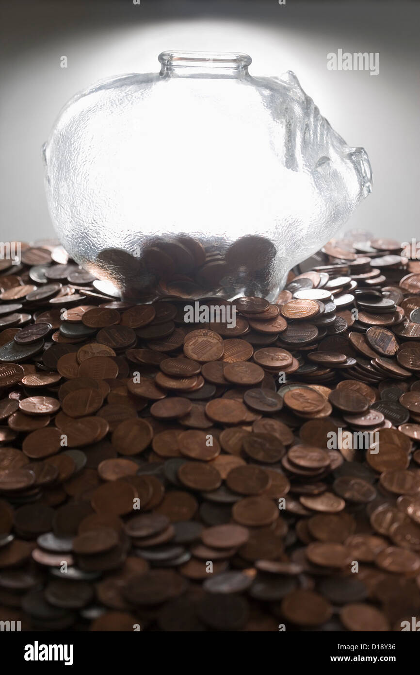 Transparent piggy bank on top of pile of coins - Stock Image