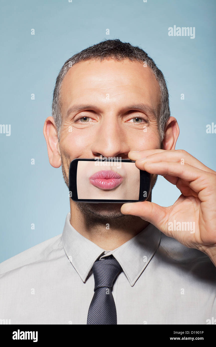 Man covering mouth with smartphone Stock Photo