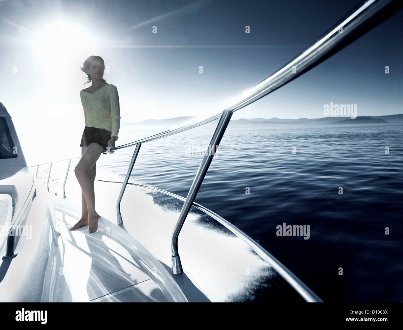 Woman standing on deck of yacht - Stock Image