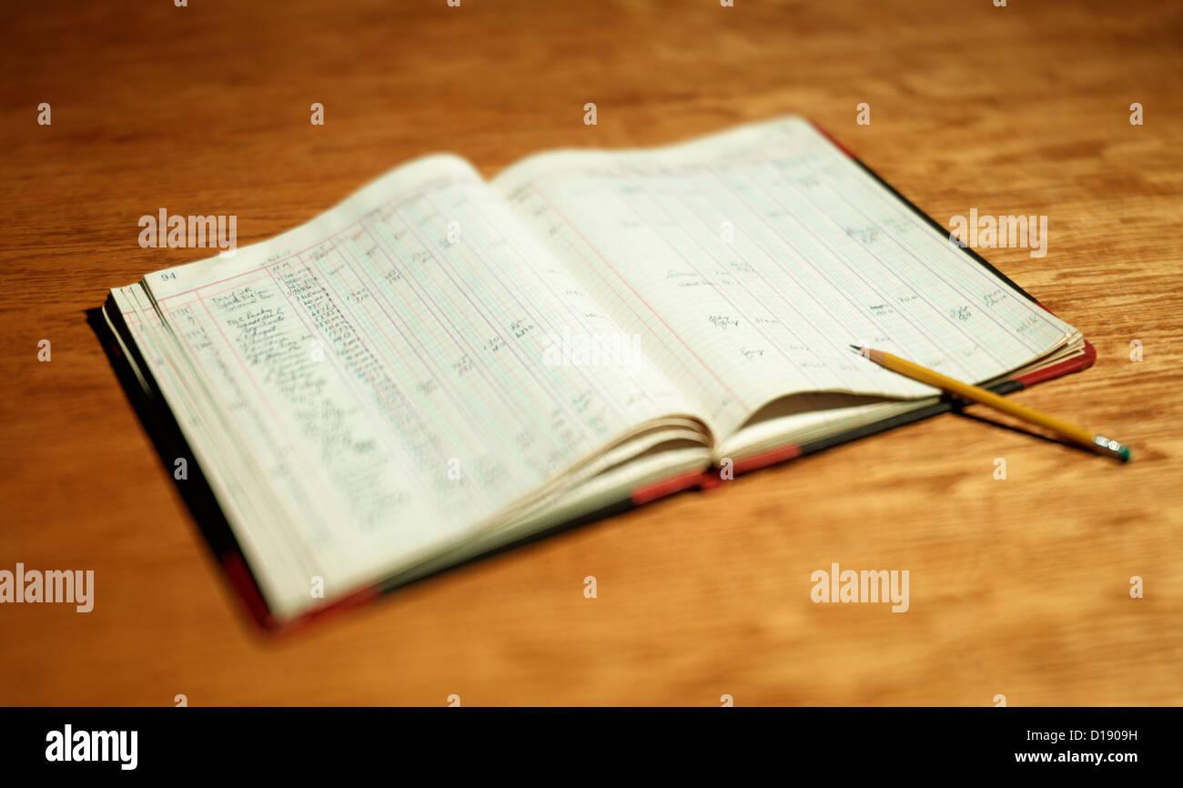 Open account book on wooden desktop - Stock Image