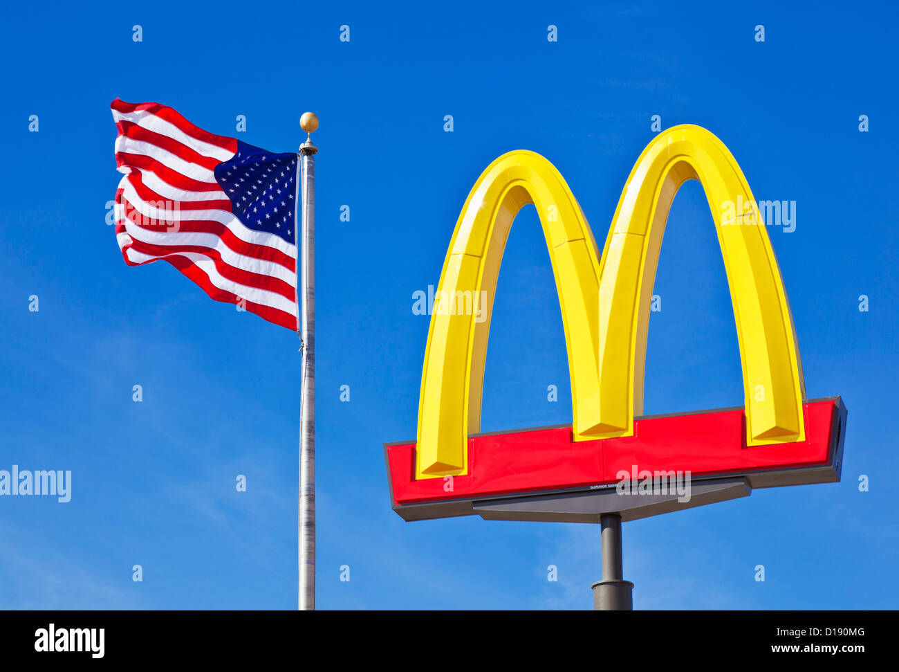 Mcdonald's Logo arches sign against a clear blue sky with an american flag stars and stripes USA United States - Stock Image