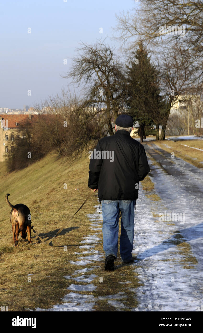 Lithuania. Man walking with his dog on an icy path. - Stock Image