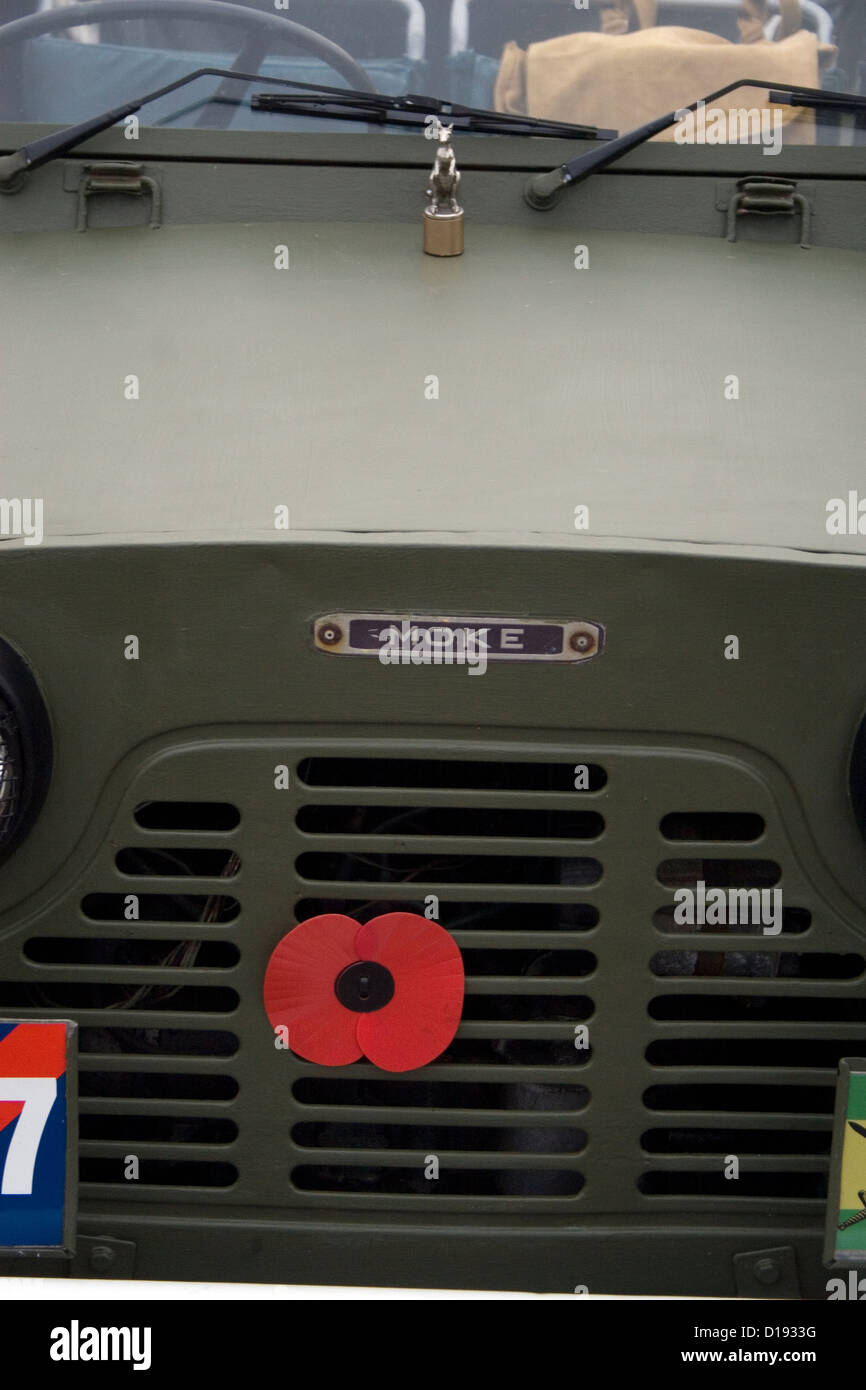 A red remembrance poppy stuck on the front of a classic military Jeep at a car show. Stock Photo