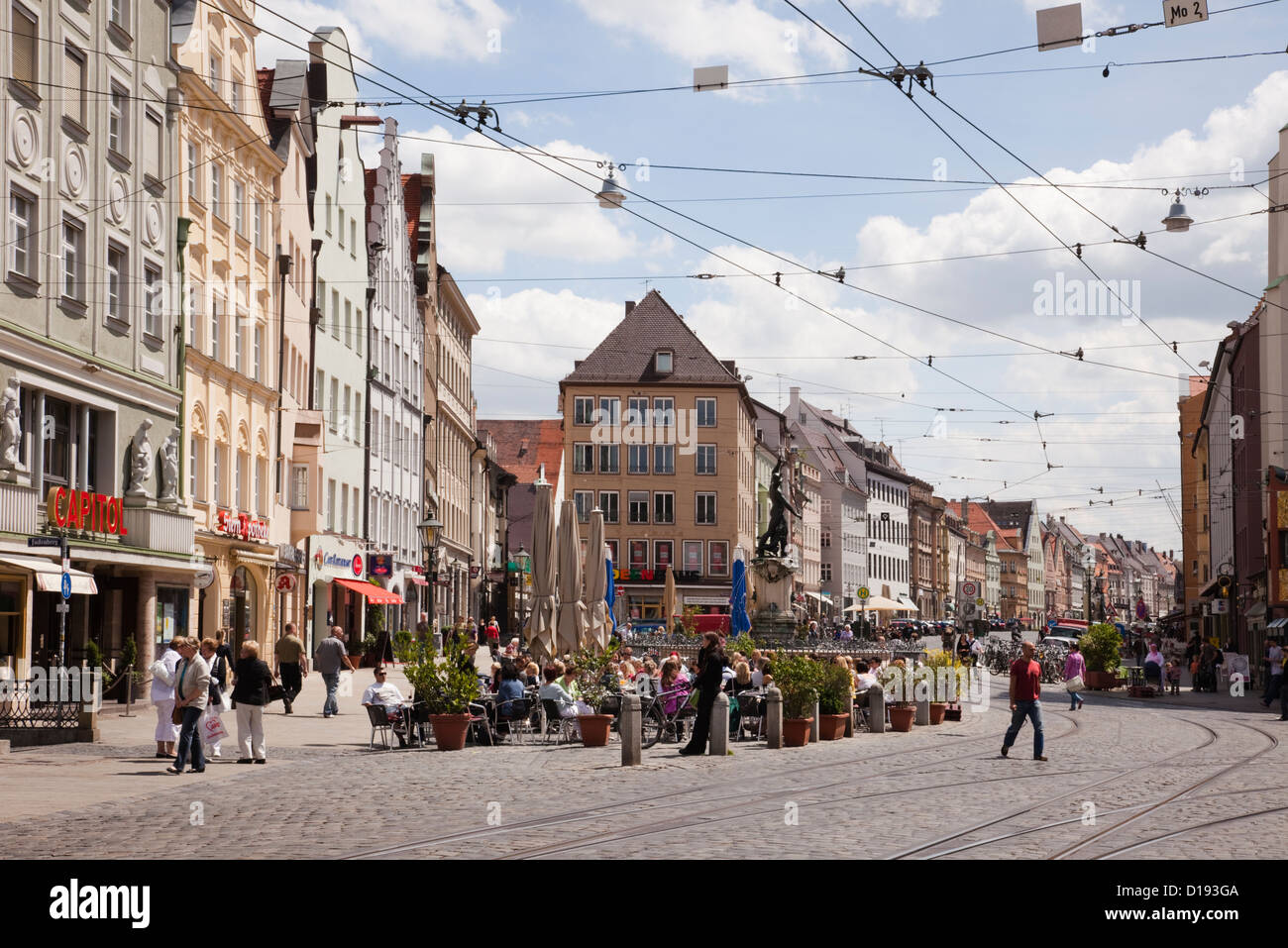 City centre street scene with overhead tram lines and people dining outside in pavement cafes in Augsburg, Bavaria, - Stock Image