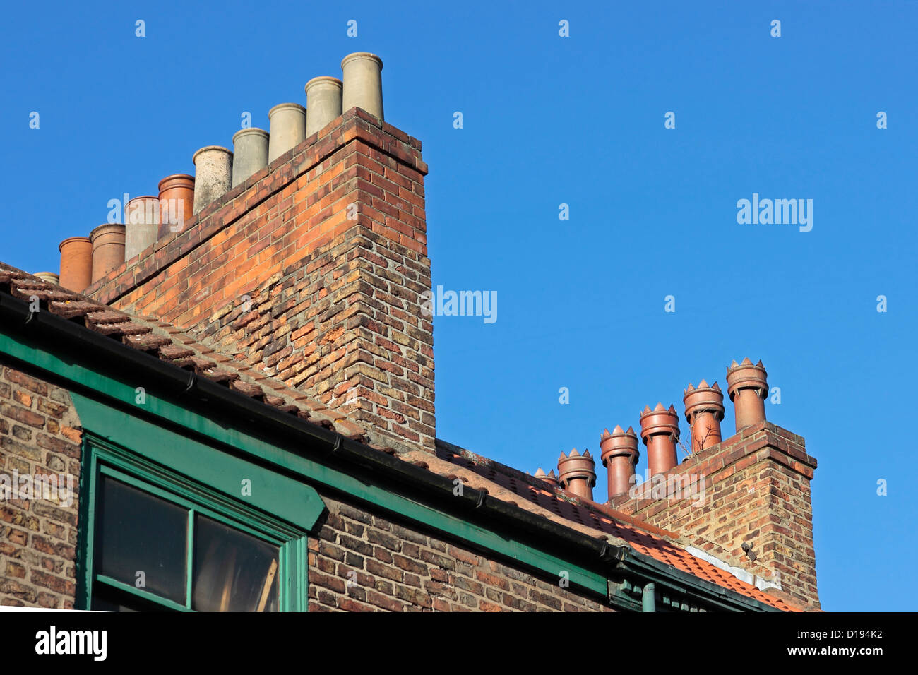 Old chimney pots on a Selby roof top against a clear blue sky - Stock Image