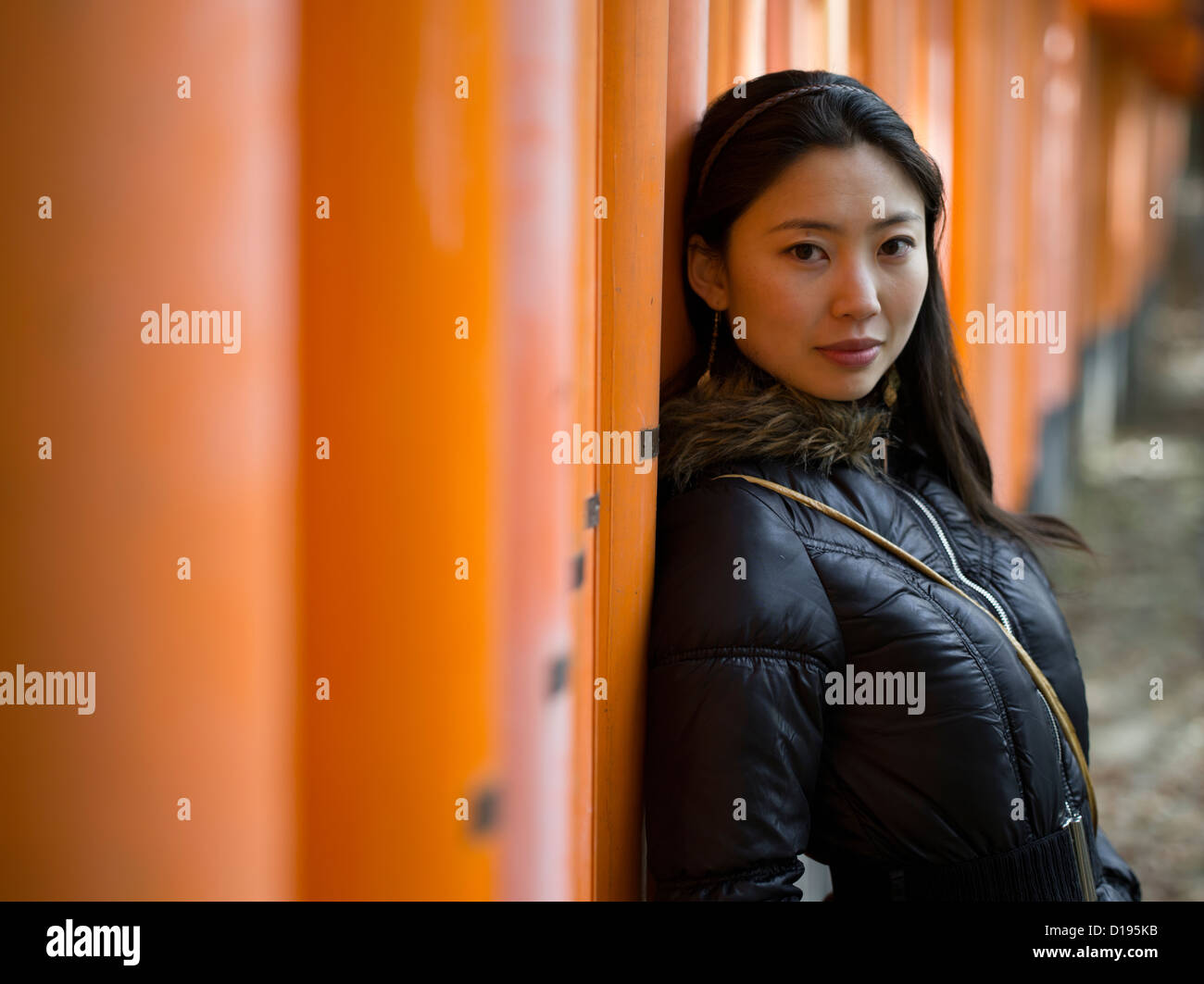Japanese woman visiting Fushimi Inari Taisha a shinto shrine with orange torii gates in Kyoto, Japan. - Stock Image