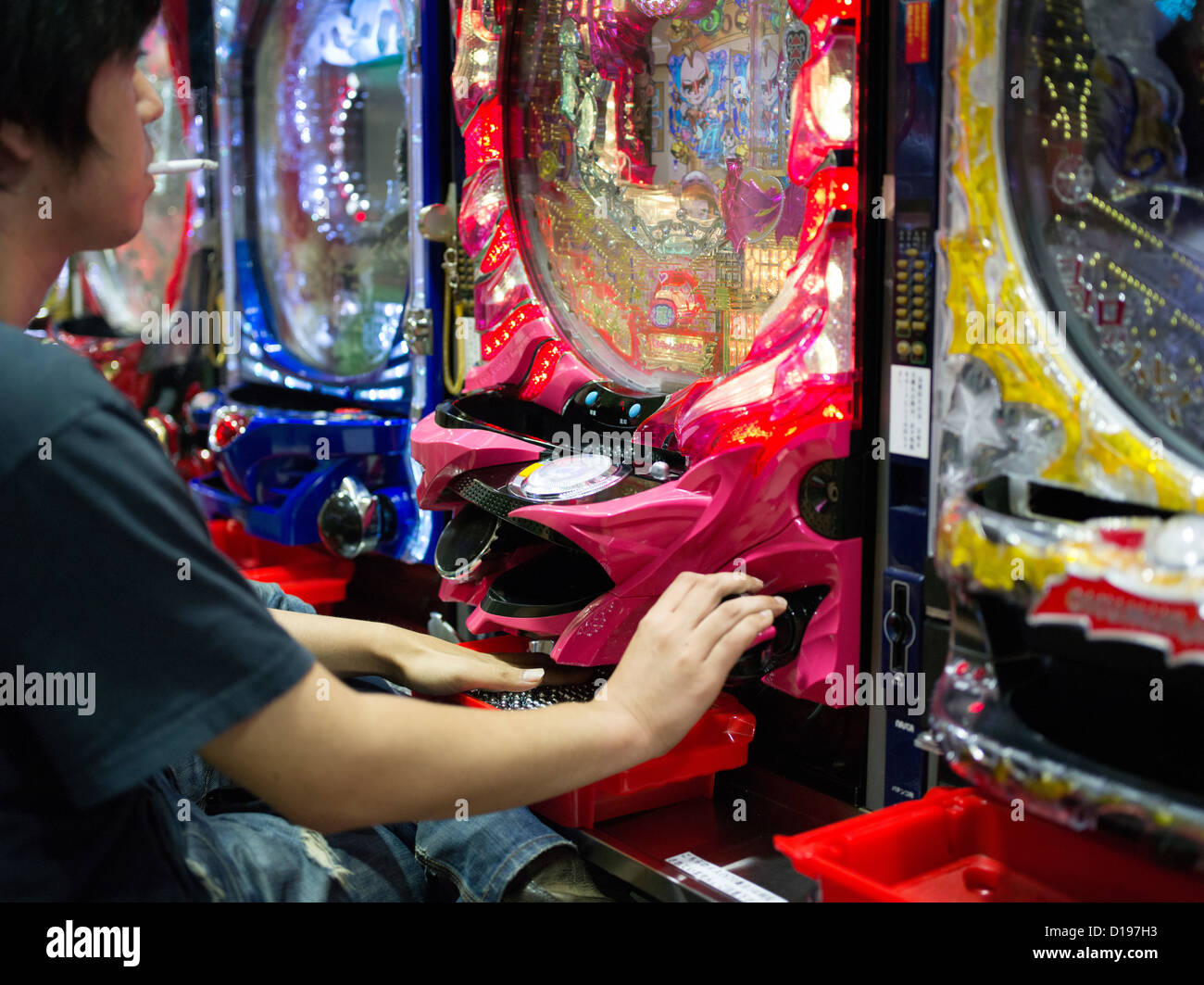 Japanese man playing pachinko and smoking in Shinjuku Tokyo - Stock Image