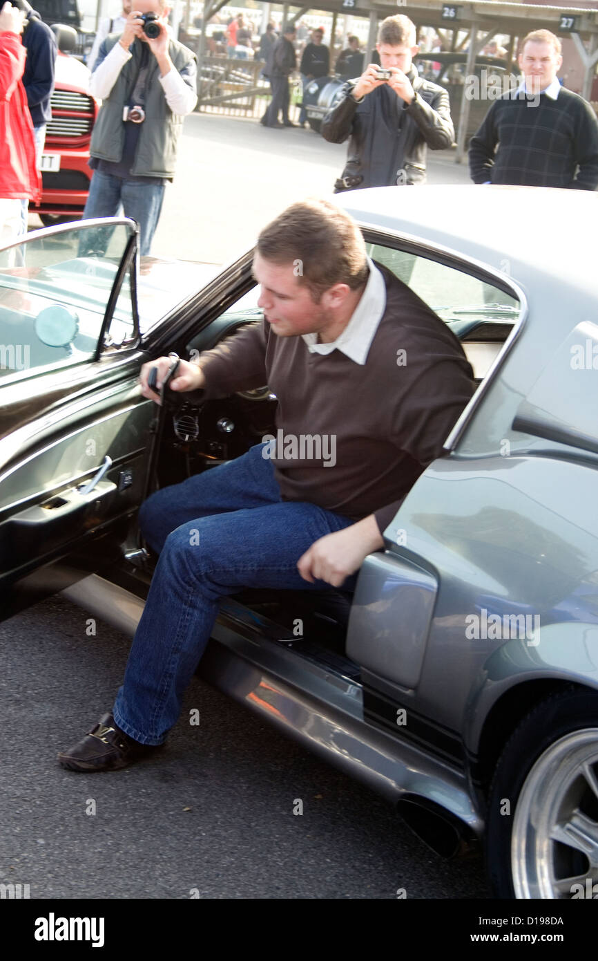 A Man Getting Out Of An American Muscle Car At A Car Show Stock
