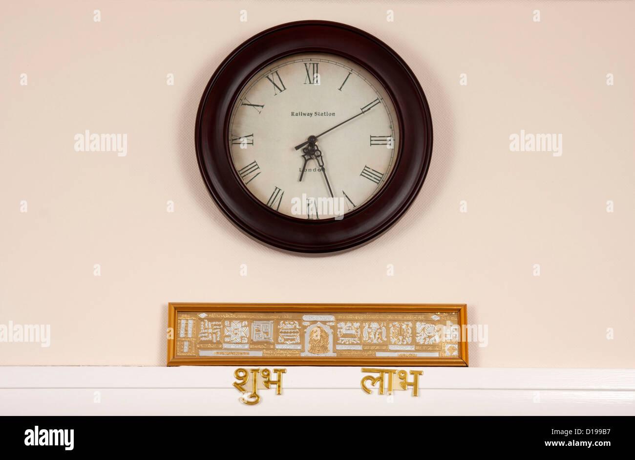 Wall clock and auspicious scripture of Jain religion. - Stock Image