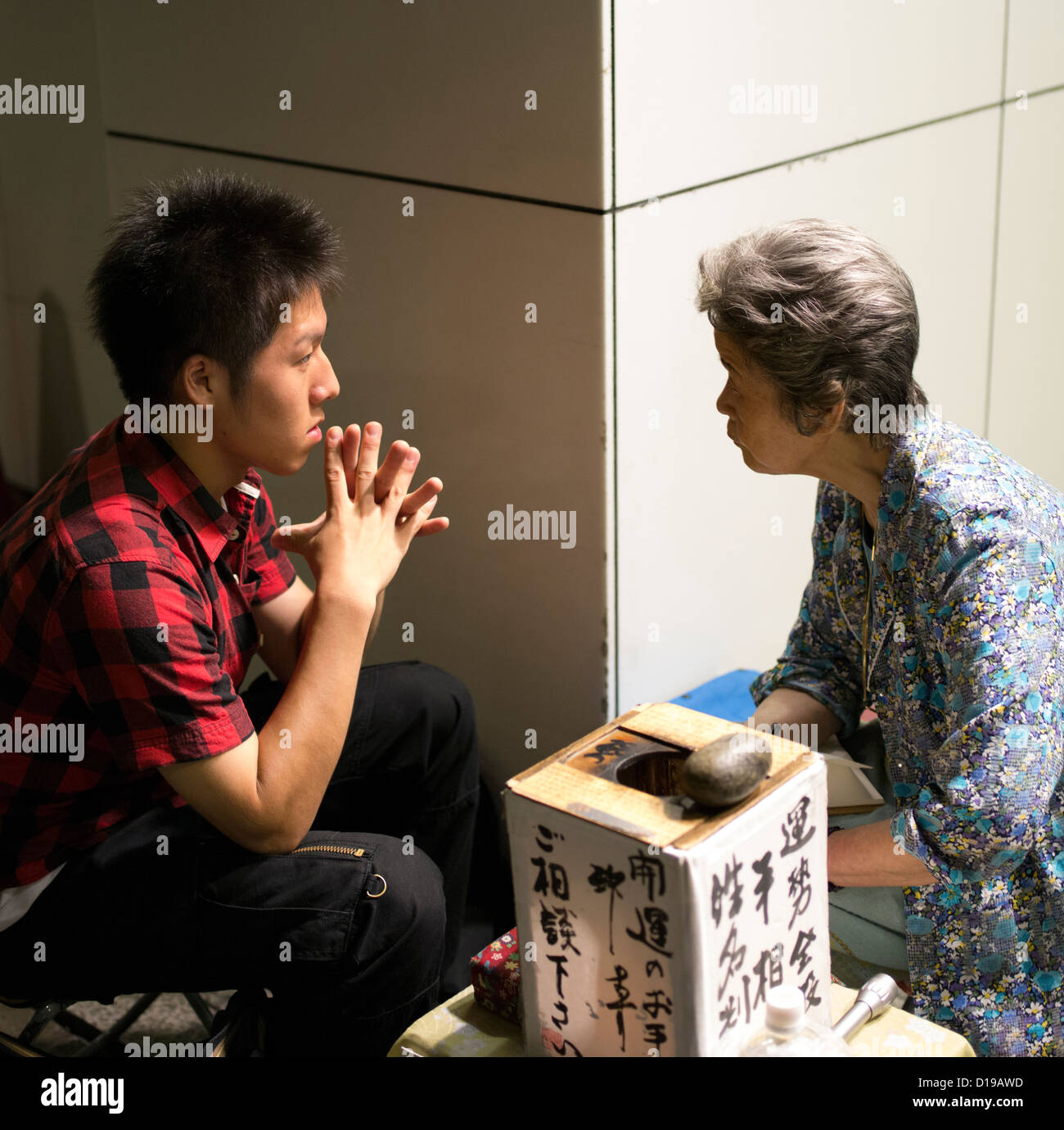 Elderly Japanese fortune teller (R) talks to young Japanese man (L) on the street in Shinjuku, Tokyo. - Stock Image