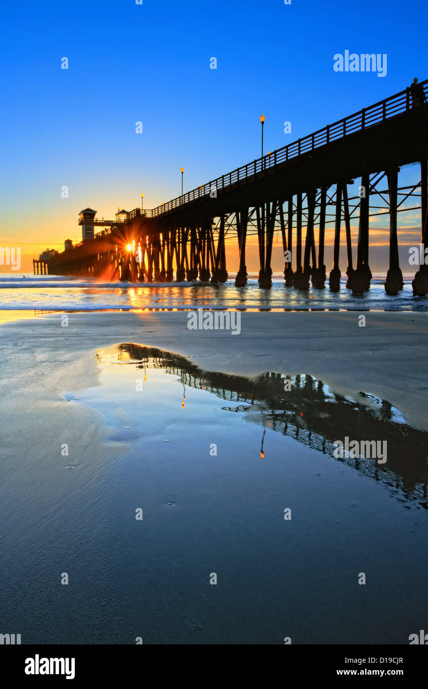 Oceanside pier and it's reflections, captured on an extremely low tide evening. - Stock Image