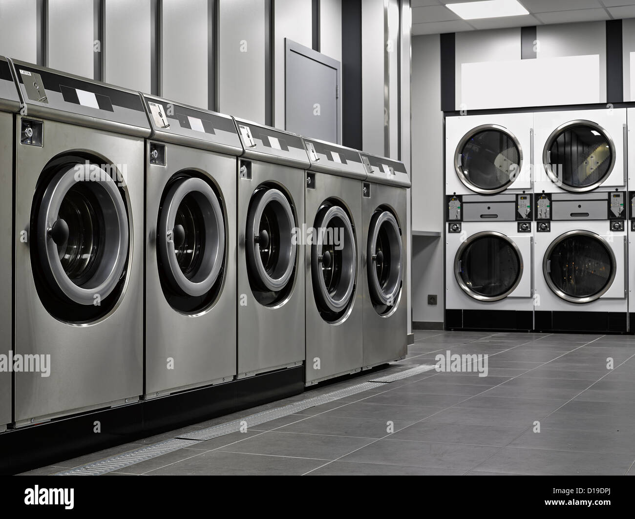 A row of industrial washing machines in a public laundromat - Stock Image