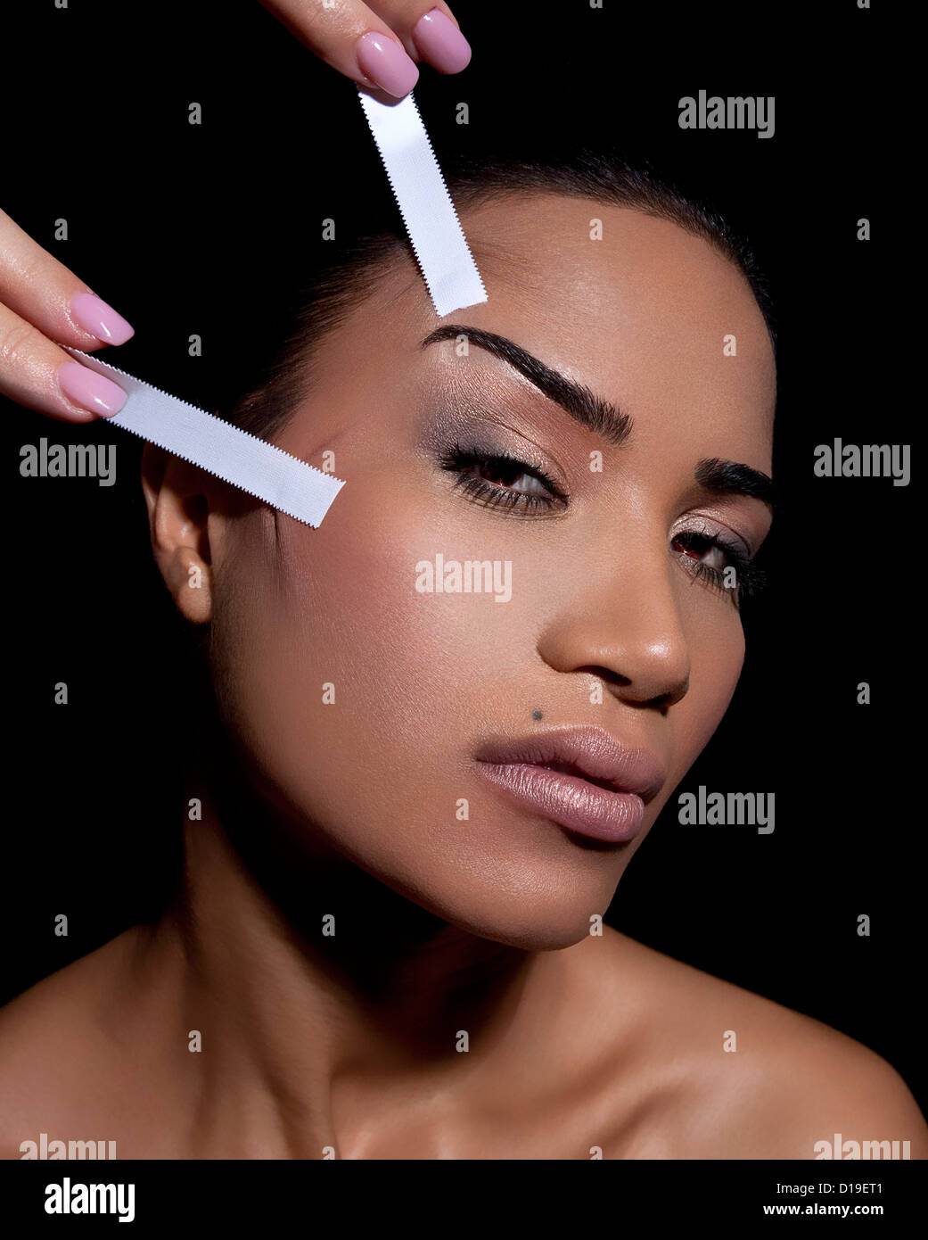 Woman having face lifted with tape - Stock Image