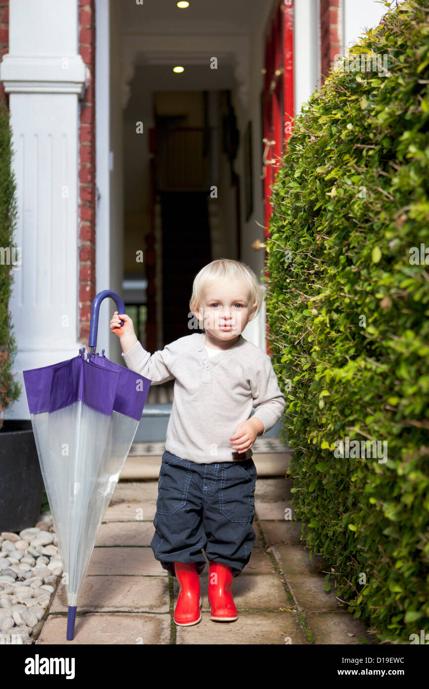 Little boy standing on front garden path with umbrella and rubber boots Stock Photo