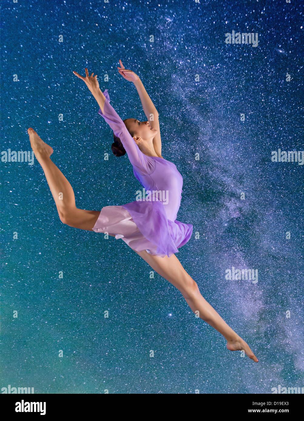 Ballerina leaping against starry night sky - Stock Image