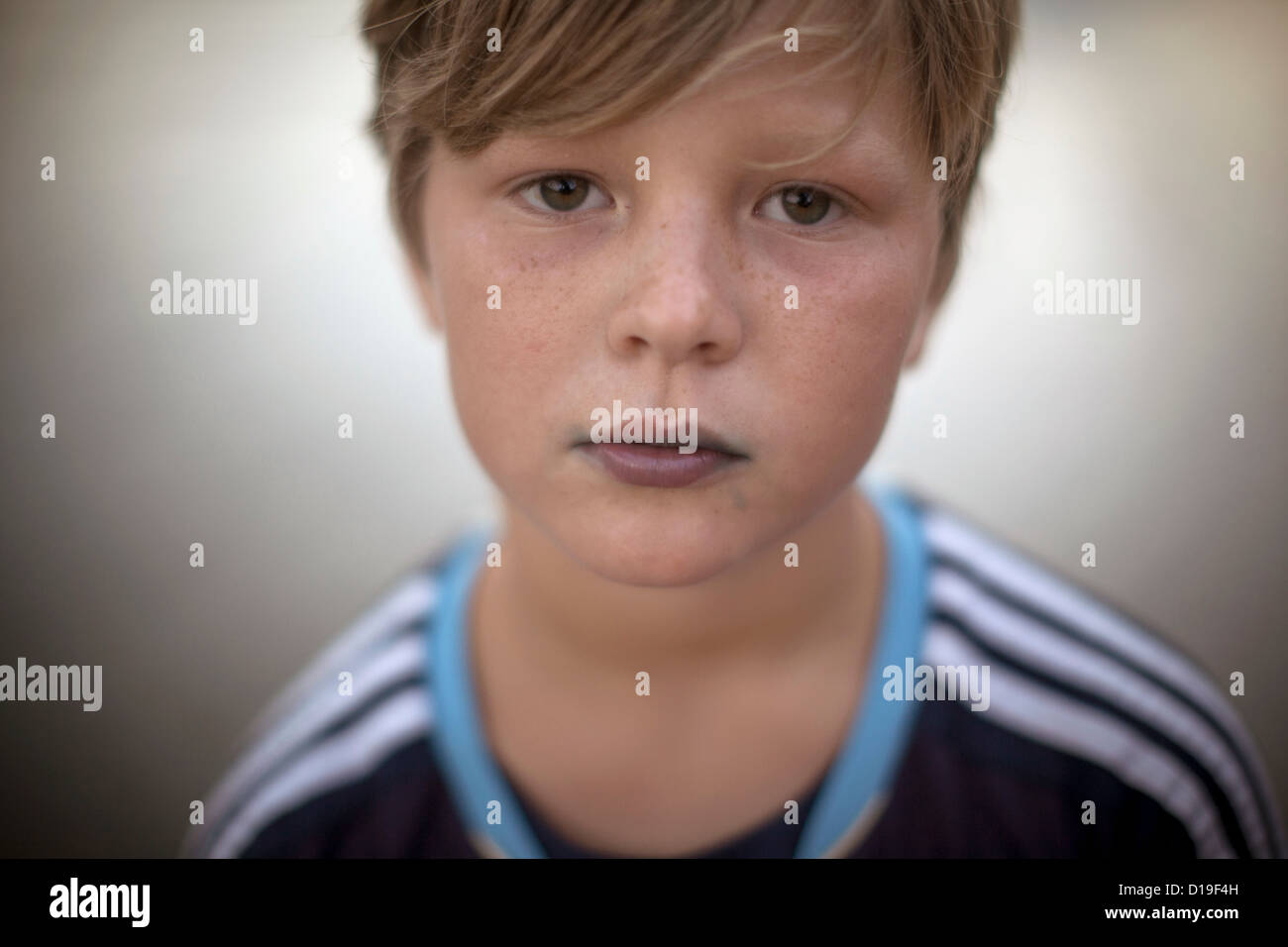 Close up portrait of boy looking at camera with blue stained lips - Stock Image