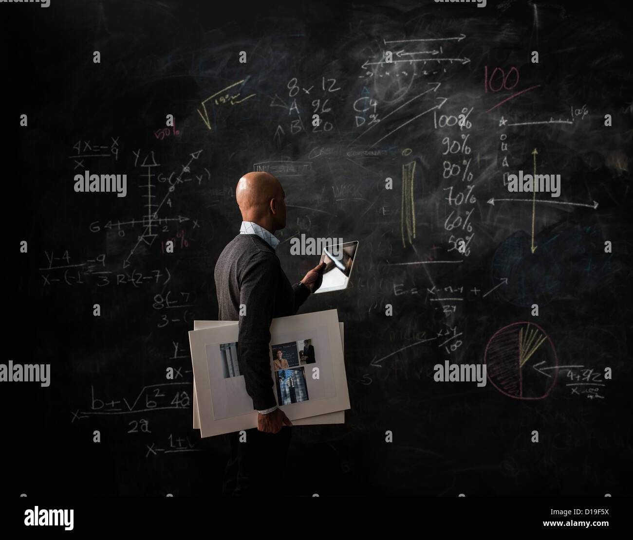 Businessman by blackboard with digital tablet and moodboard - Stock Image