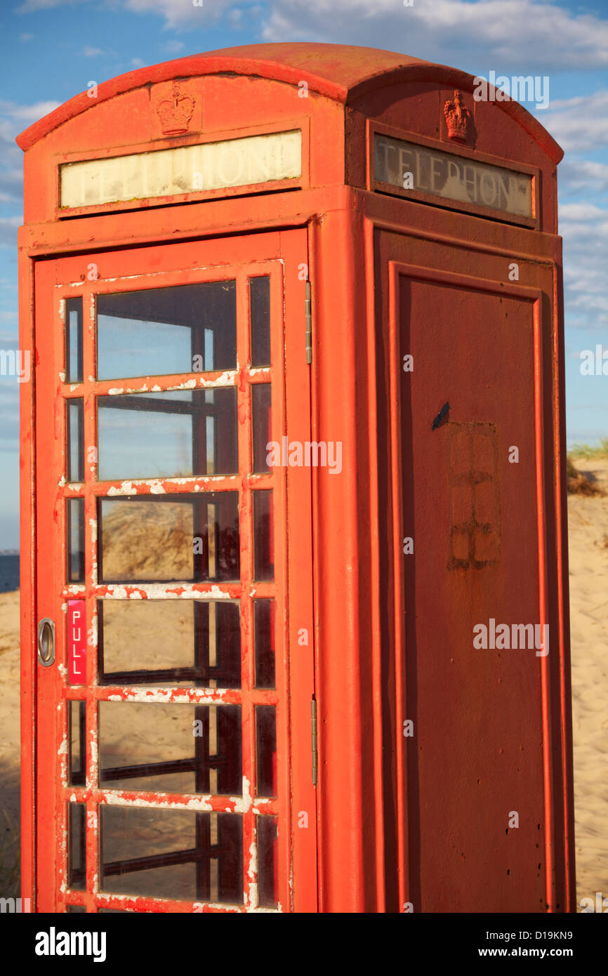 Faded and peeling red telephone box at Studland, Dorset in the evening light - Stock Image