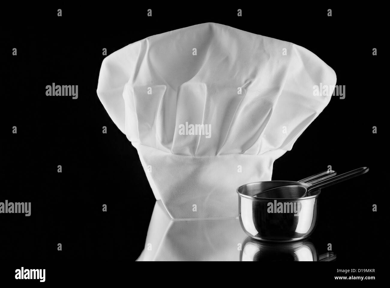 Chef's hat with measuring cup reflecting on mirror with black background - Stock Image