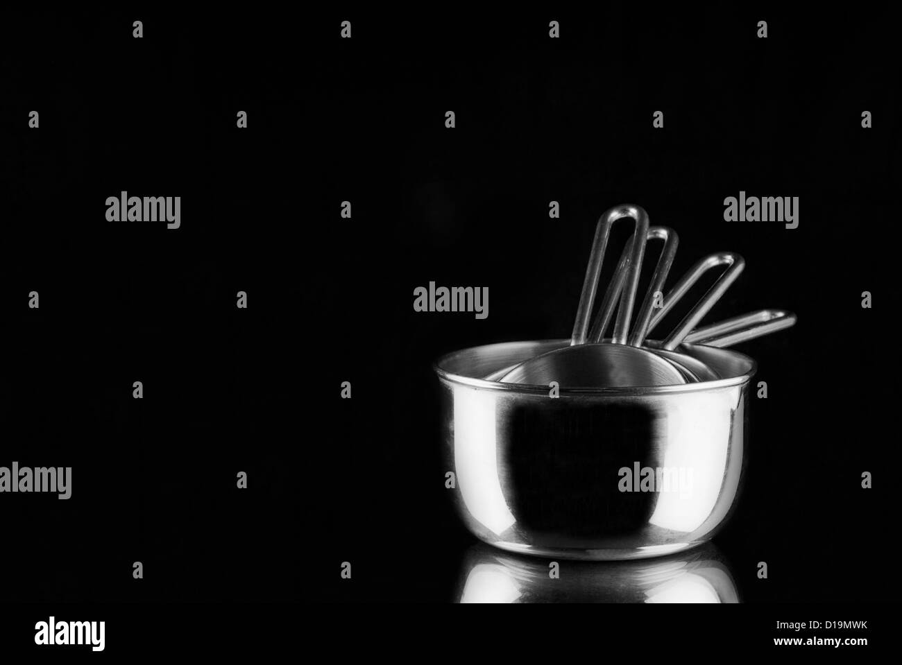 Stainless steel measuring cups on mirror with black background - Stock Image