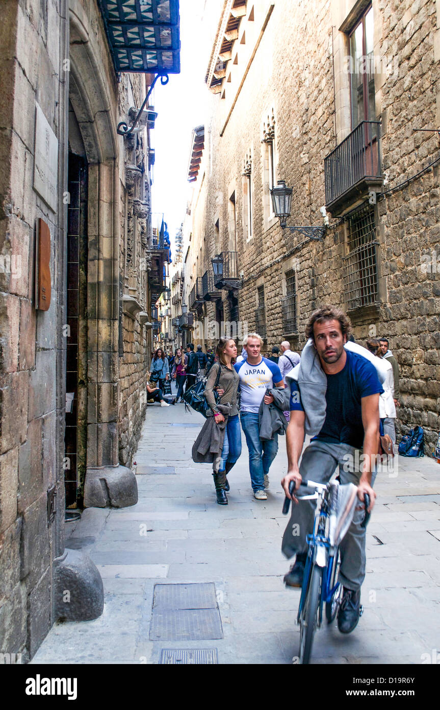 Cyclists & sightseers vie for space in the narrow medieval streets of the Barri Gotic district of Barcelona, - Stock Image