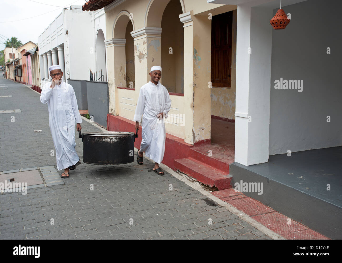 Two Muslim men carry a large cooking pot down a street in Galle Fort Sri Lanka - Stock Image