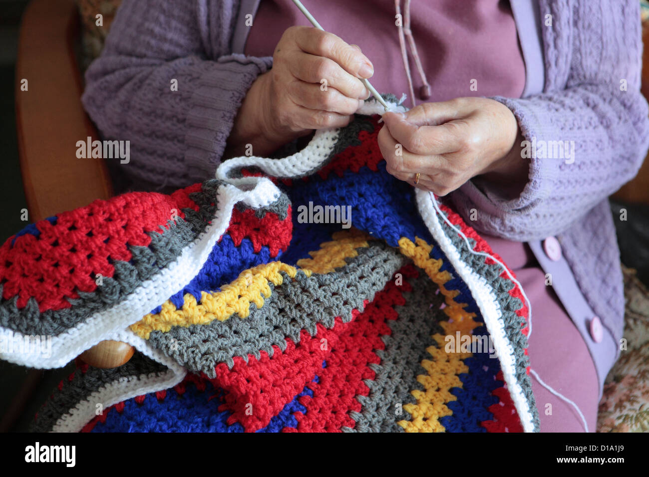 Elderly woman crocheting colorful blanket for charity at home, Suffolk, UK - Stock Image