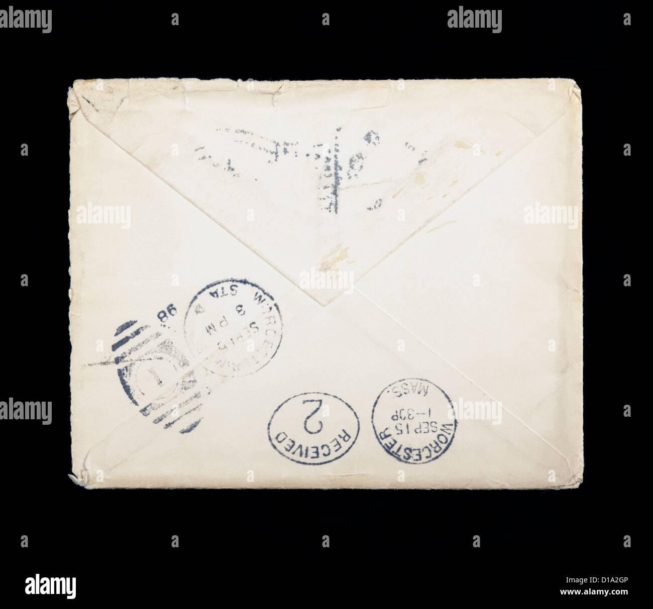 Old stamped envelope shot on black background - Stock Image