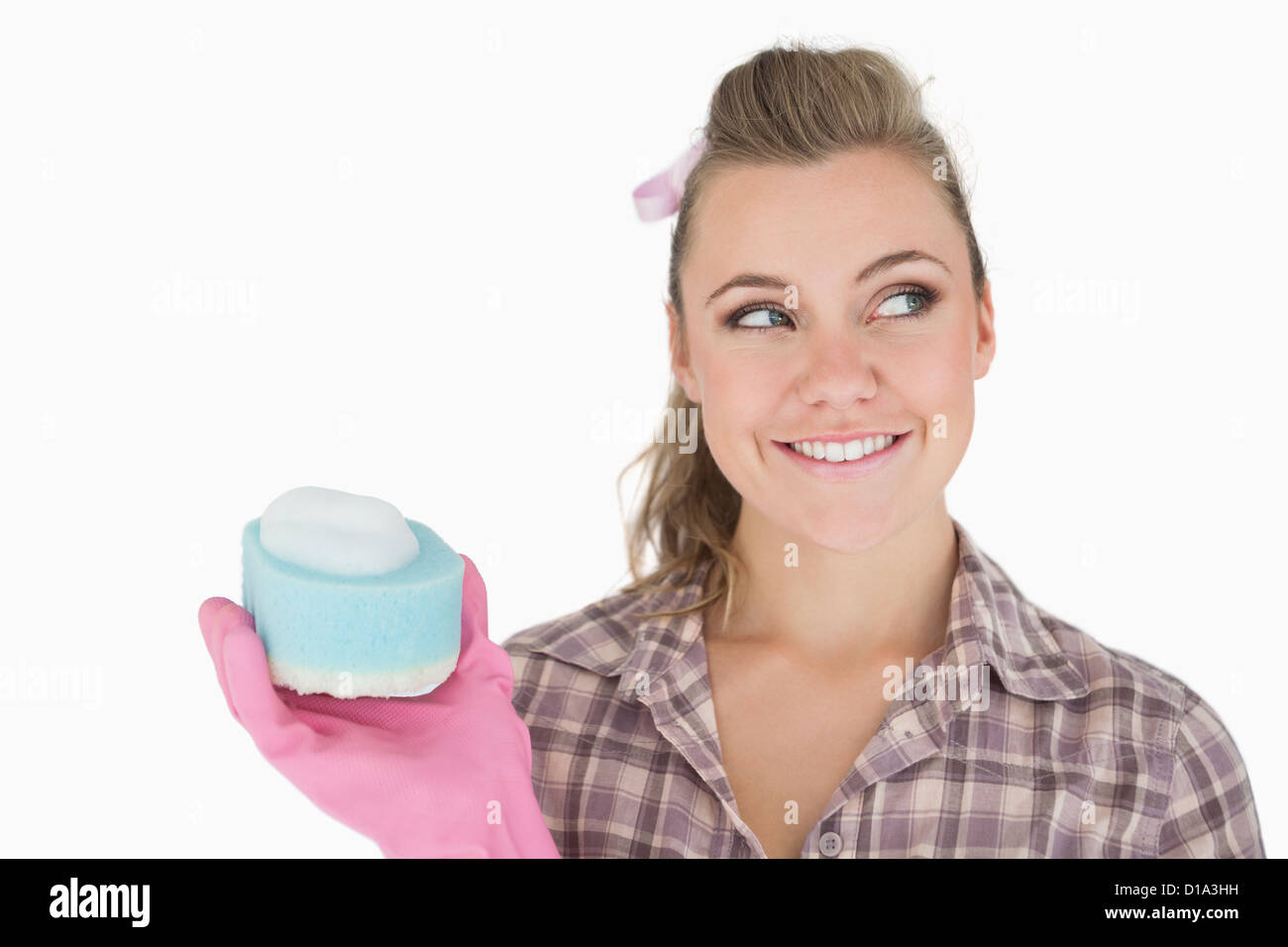 Smiling woman holding soap suds over sponge - Stock Image