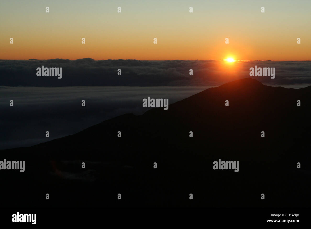 Sunrise over the clouds from Haleakala volcano, Maui, Hawaii Stock Photo