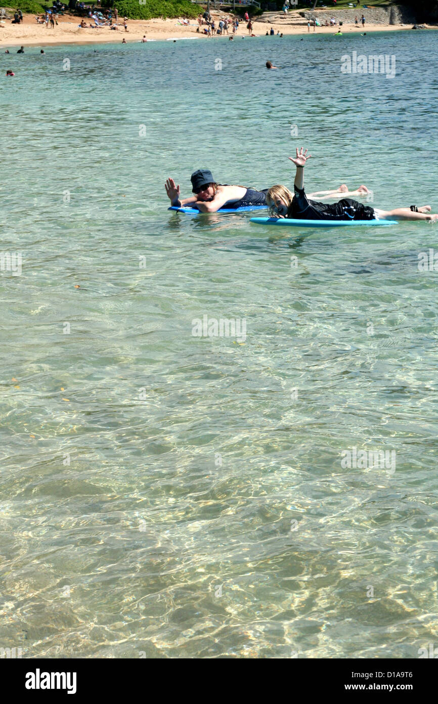 Woman and girl paddling on boogie boards in clear blue water of Kapalua Bay, Maui, Hawaii Stock Photo