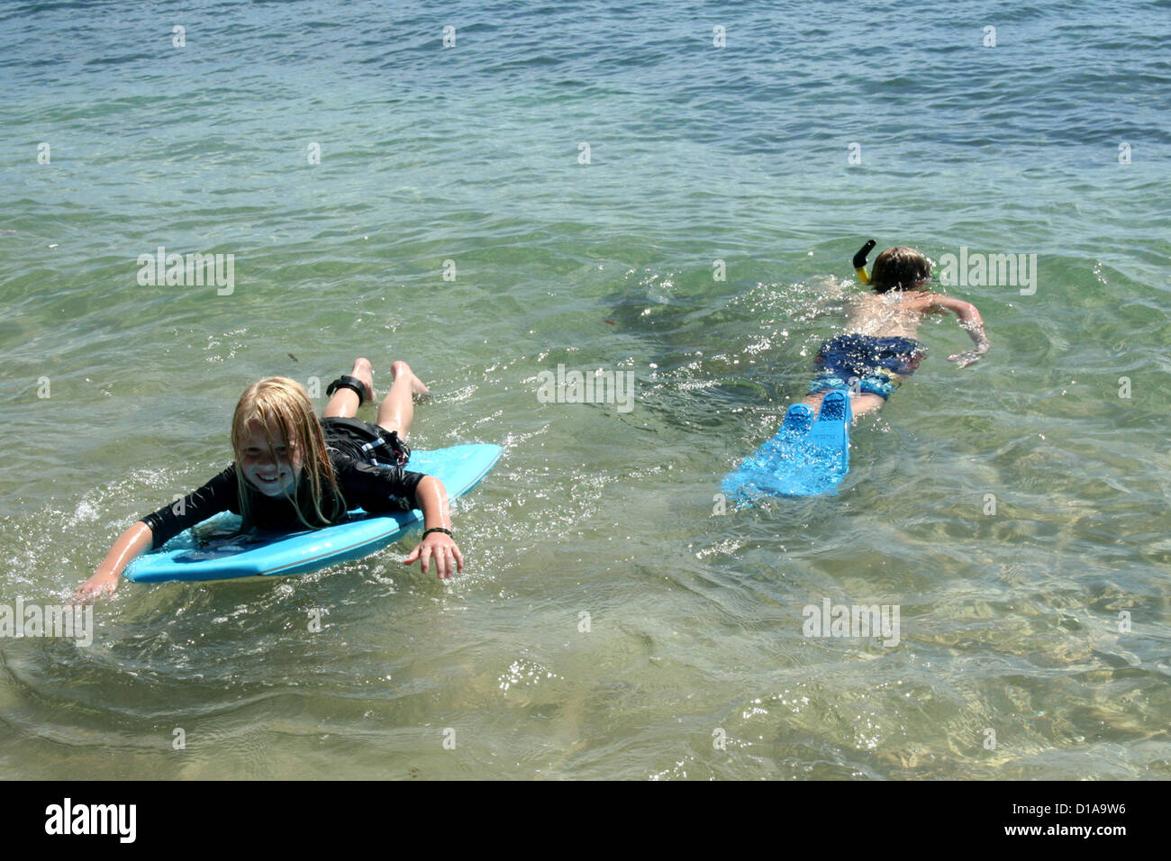 Kids snorkeling and boogie boarding in clear blue water of Kapalua beach, Maui, Hawaii Stock Photo