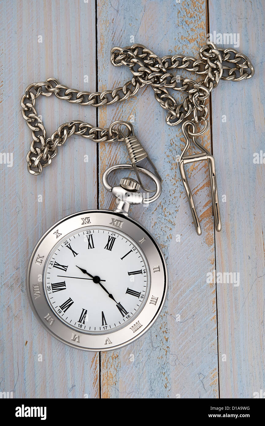 Photo of silver vintage pocket watch with chain on wooden background - Stock Image