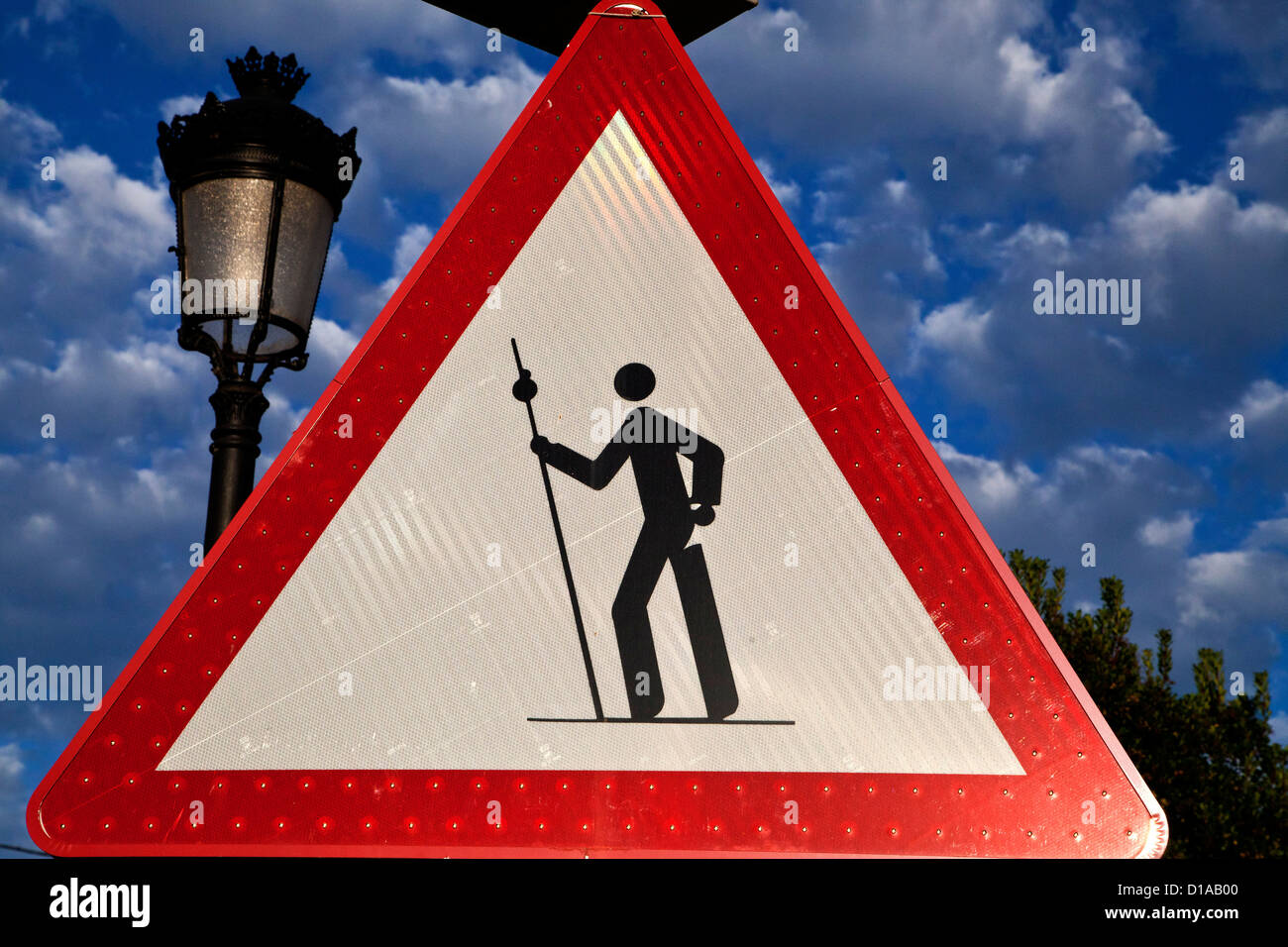 Stylized pilgrim symbol on a yield sign, on the Camino to Santiago de Compostela Spain - Stock Image