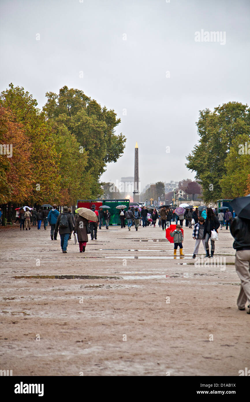 people walking in the 'jardin des tuileries' gardens near the Louve, Paris France, with umbrellas and puddles. - Stock Image