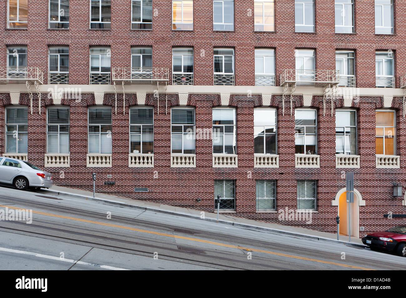 Brick building on heavy sloped street - San Francisco, California USA - Stock Image