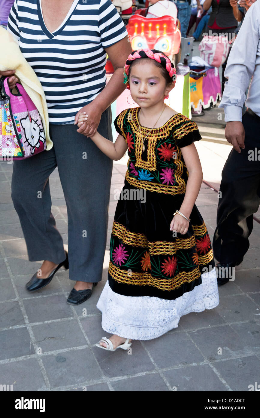 Dignified young Mexican girl dressed as Guadalupe in a velvet dress with beautiful colored embroidery,  accompanied - Stock Image