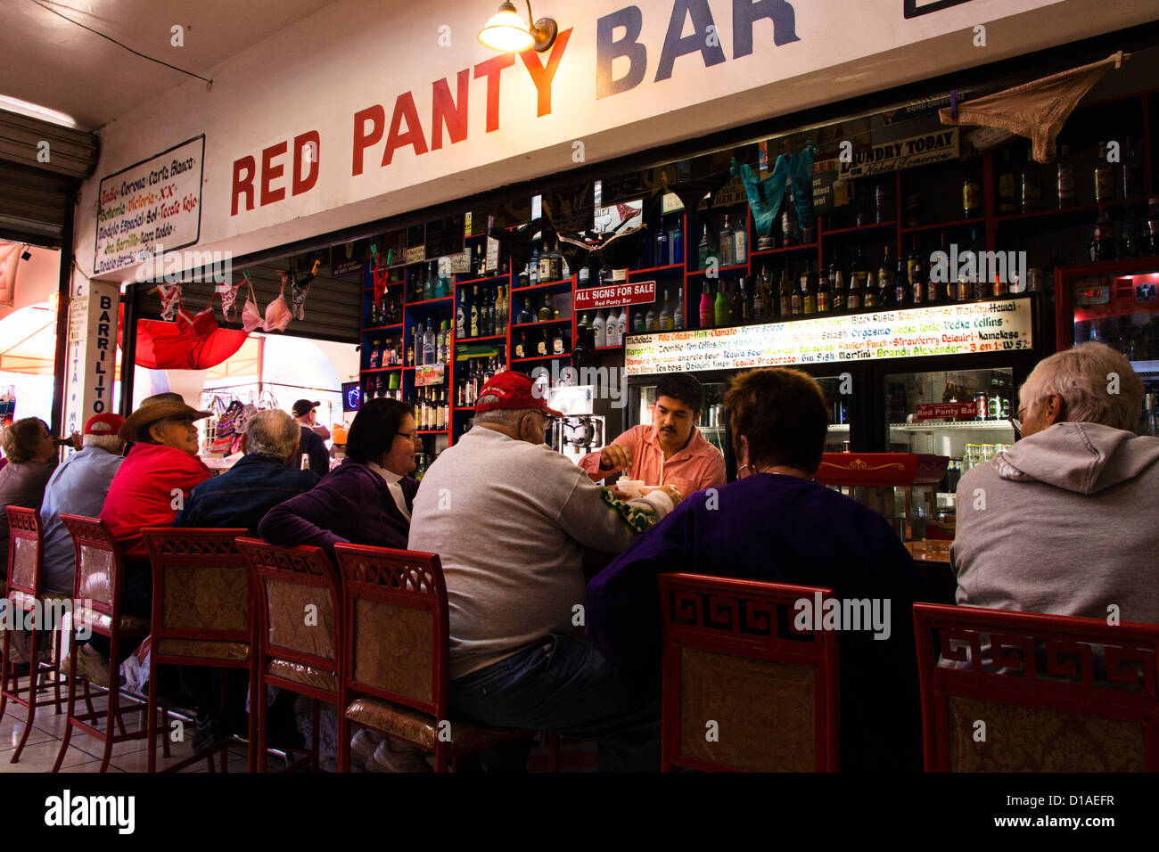 Senior citizens sitting on bar stools at the Red Panty Bar in Nuevo Progreso, Tamaulipas, Mexico.  It's 10:30 A.M. Stock Photo
