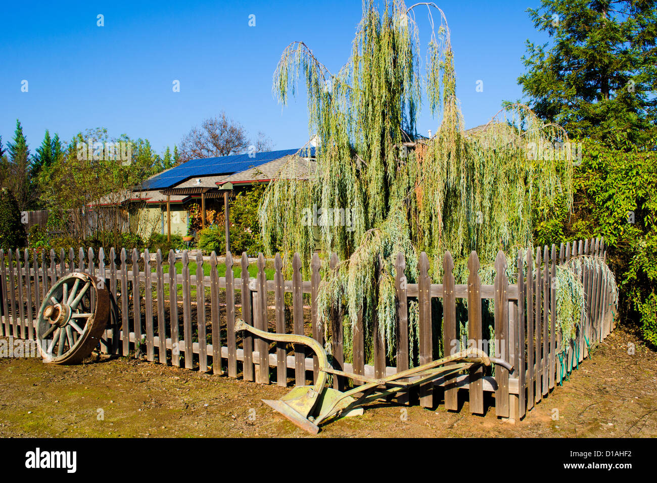 Wagon Wheel And Old Plow As Yard Art In Front Of A Picket Fence And Stock Photo Alamy