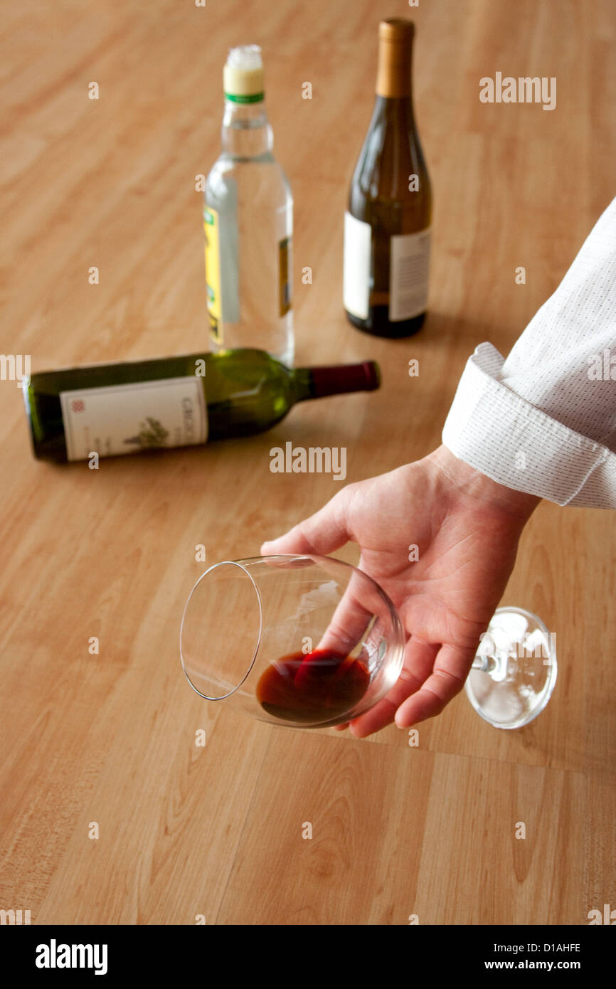Drunken man holding a glass of red wine - Stock Image