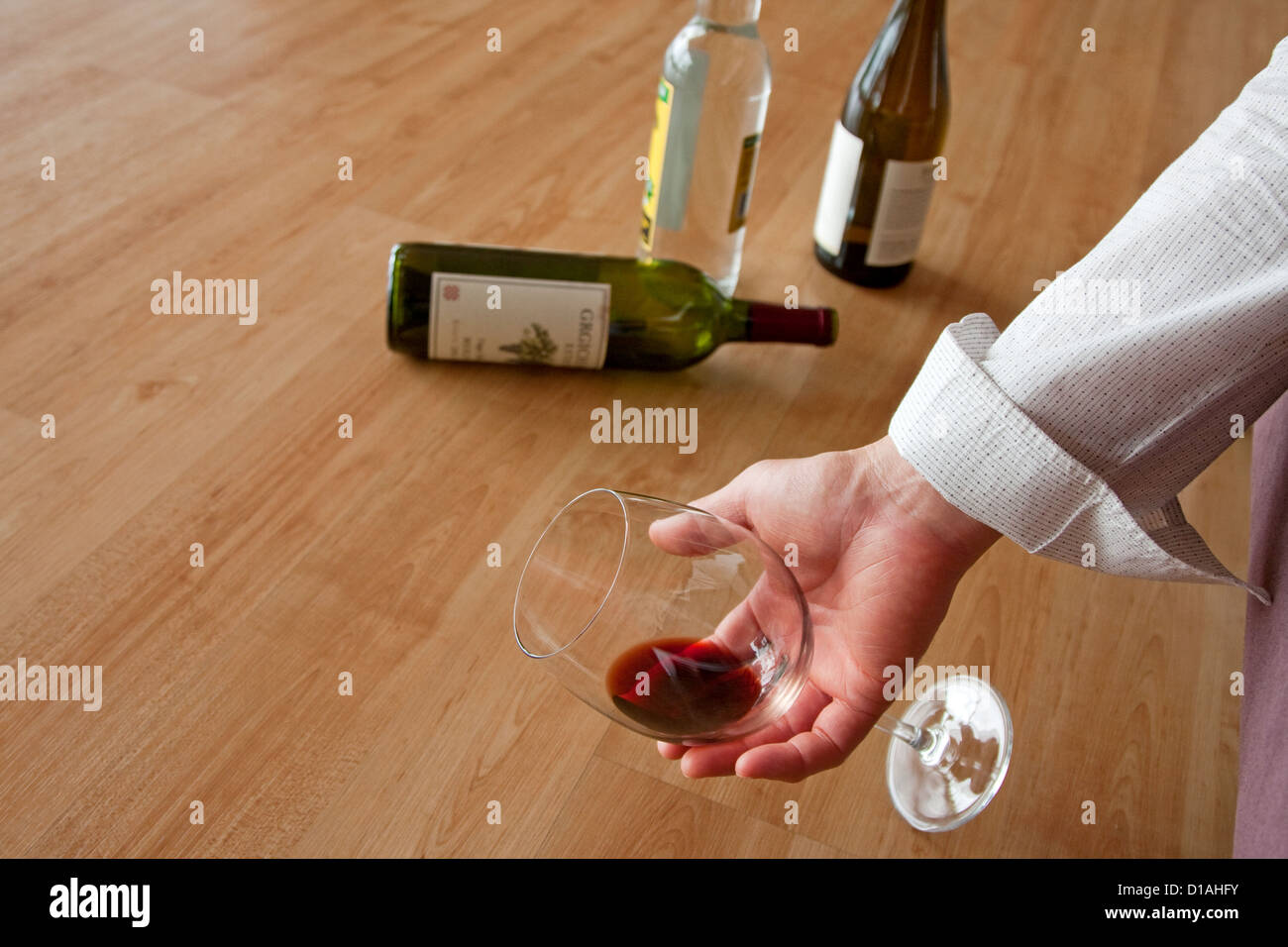 Drunken male holding a glass of red wine - Stock Image